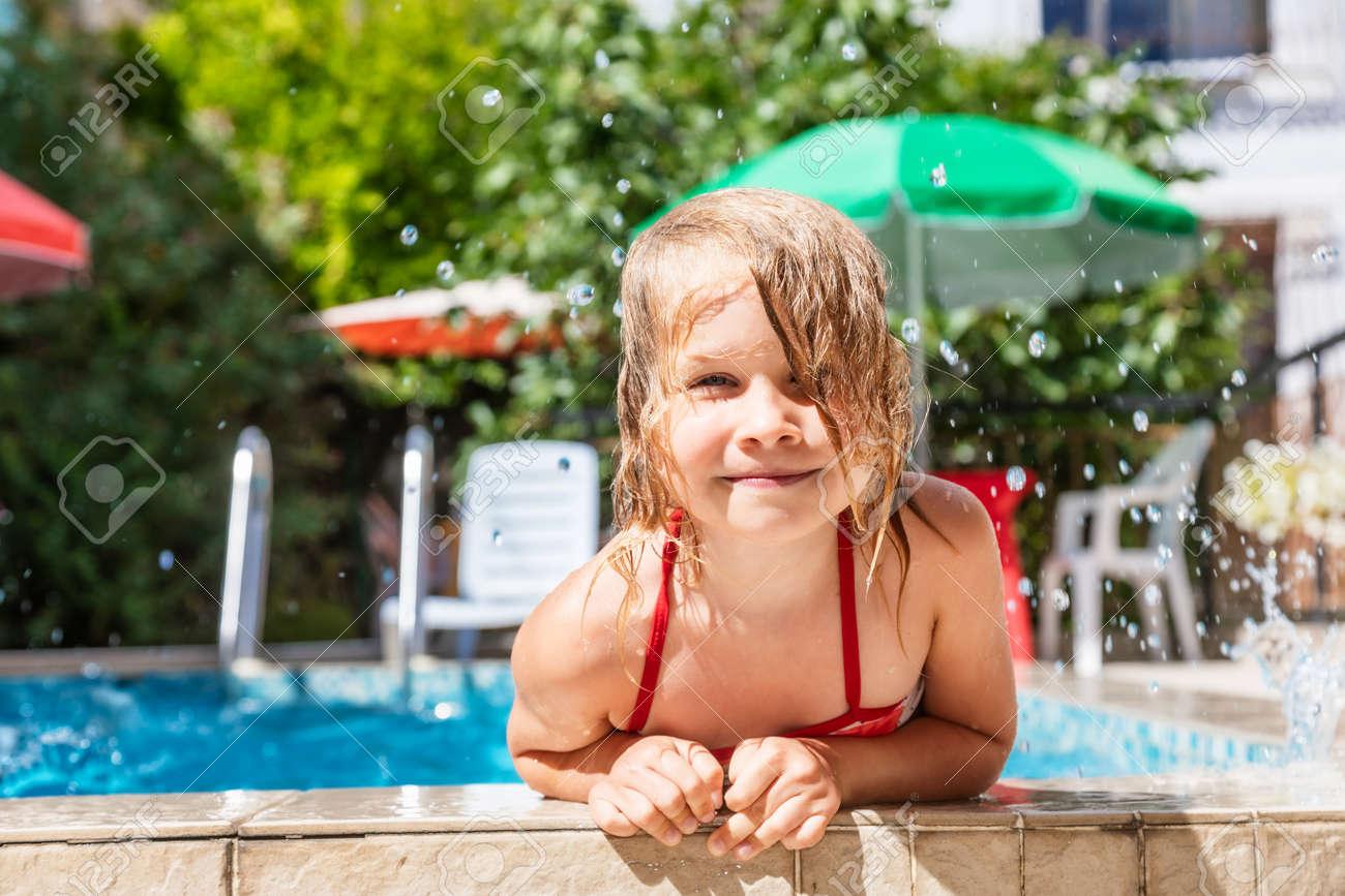 Happy little girl having fun playing in outdoor pool splashing water during summer holidays - 167056433