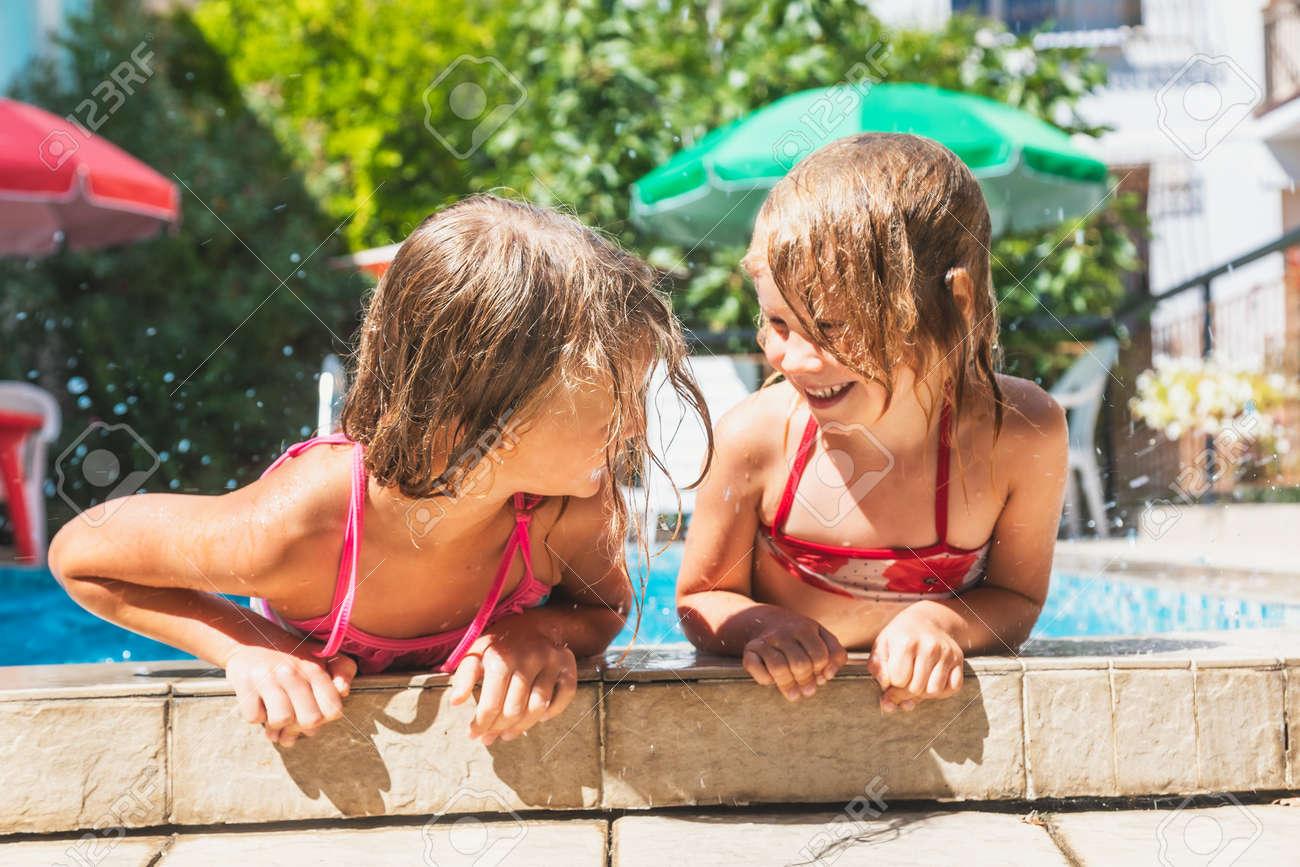 Happy little girls having fun playing in outdoor pool splashing water during summer holidays - 167056431