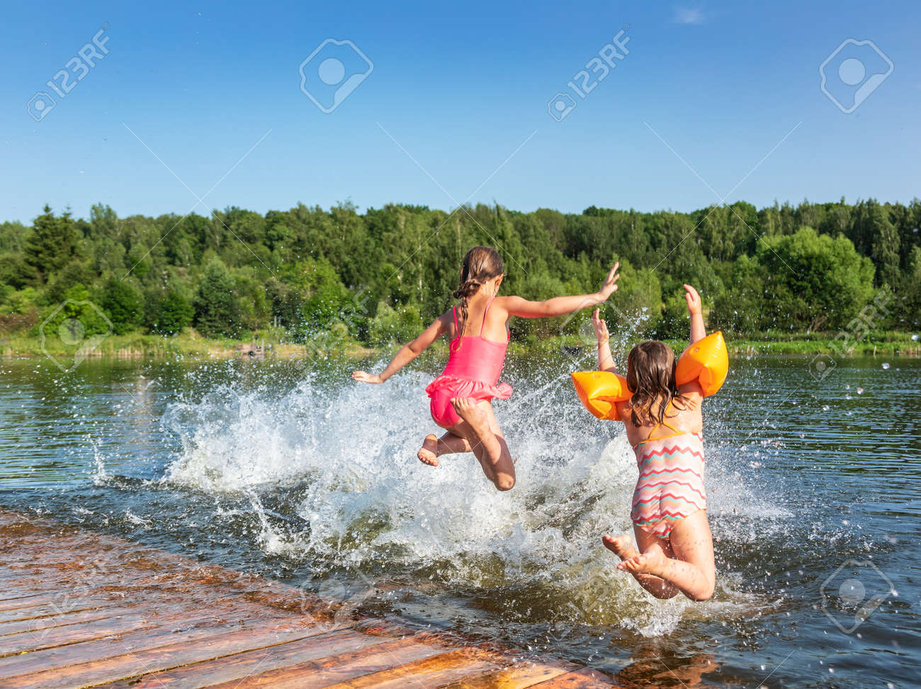 Happy little girls having fun playing in a lake jumping into water during summer holidays - 167176342