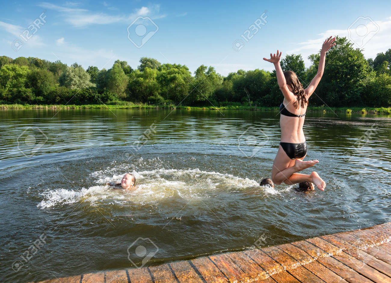 Happy little girls having fun playing in a lake jumping into water during summer holidays - 167176302