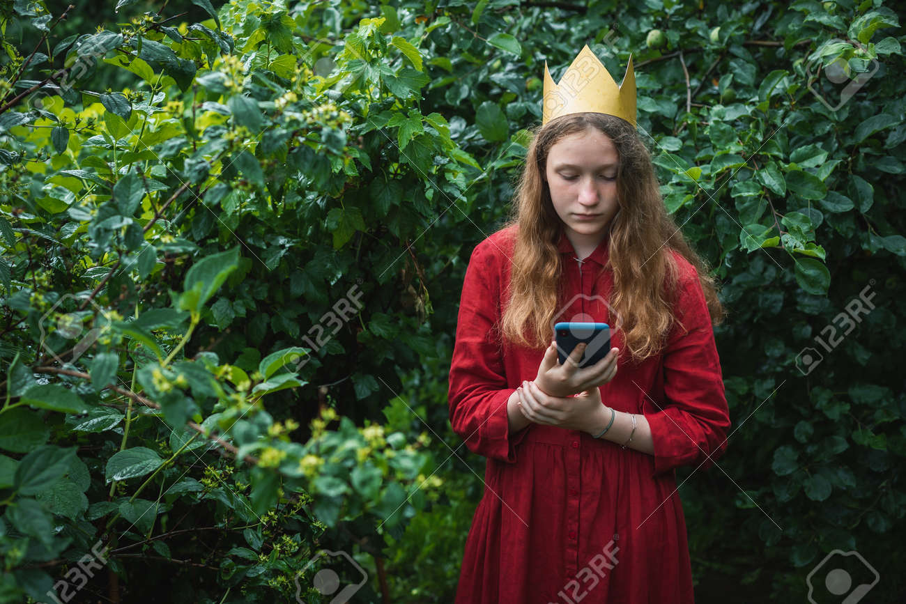Preteen girl wearing red dress and paper crown standing in wet garden using phone - 167164725