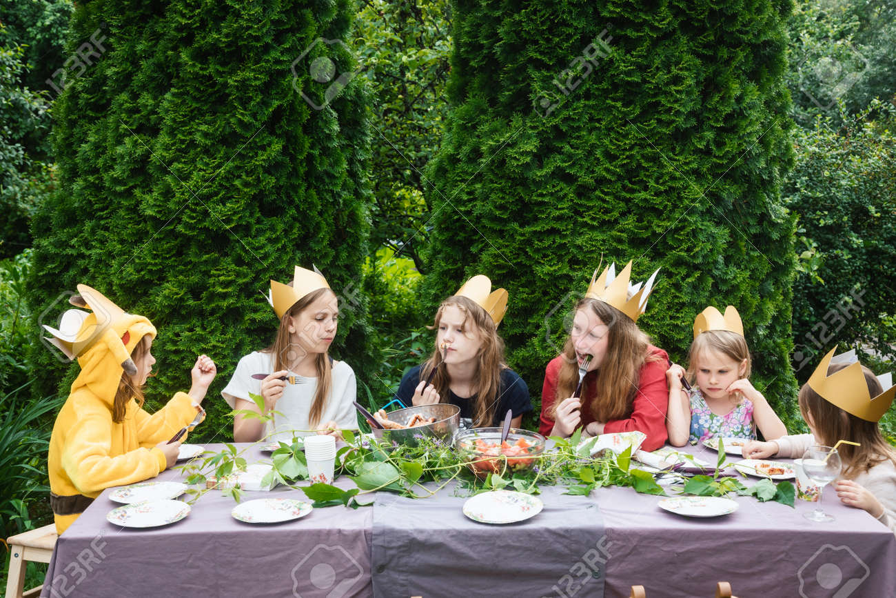Children wearng paper crowns sitting by decorated table eating grilled sausages celebrating birthday party in a green garden - 167165492