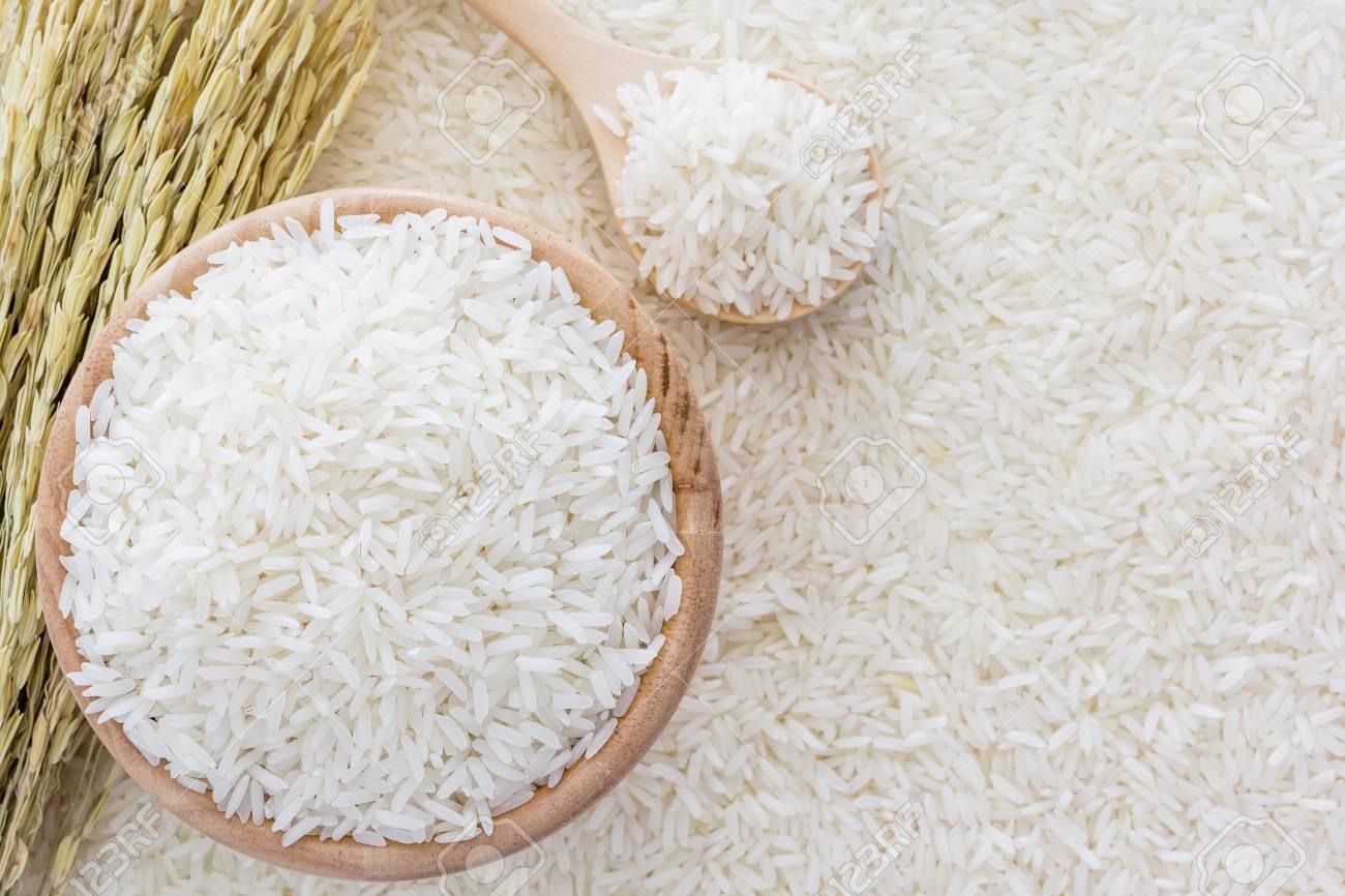 66833429-arroz-blanco-en-un-taz%C3%B3n-y-una-bolsa-una-cuchara-y-arroz-planta-de-madera-en-el-fondo-