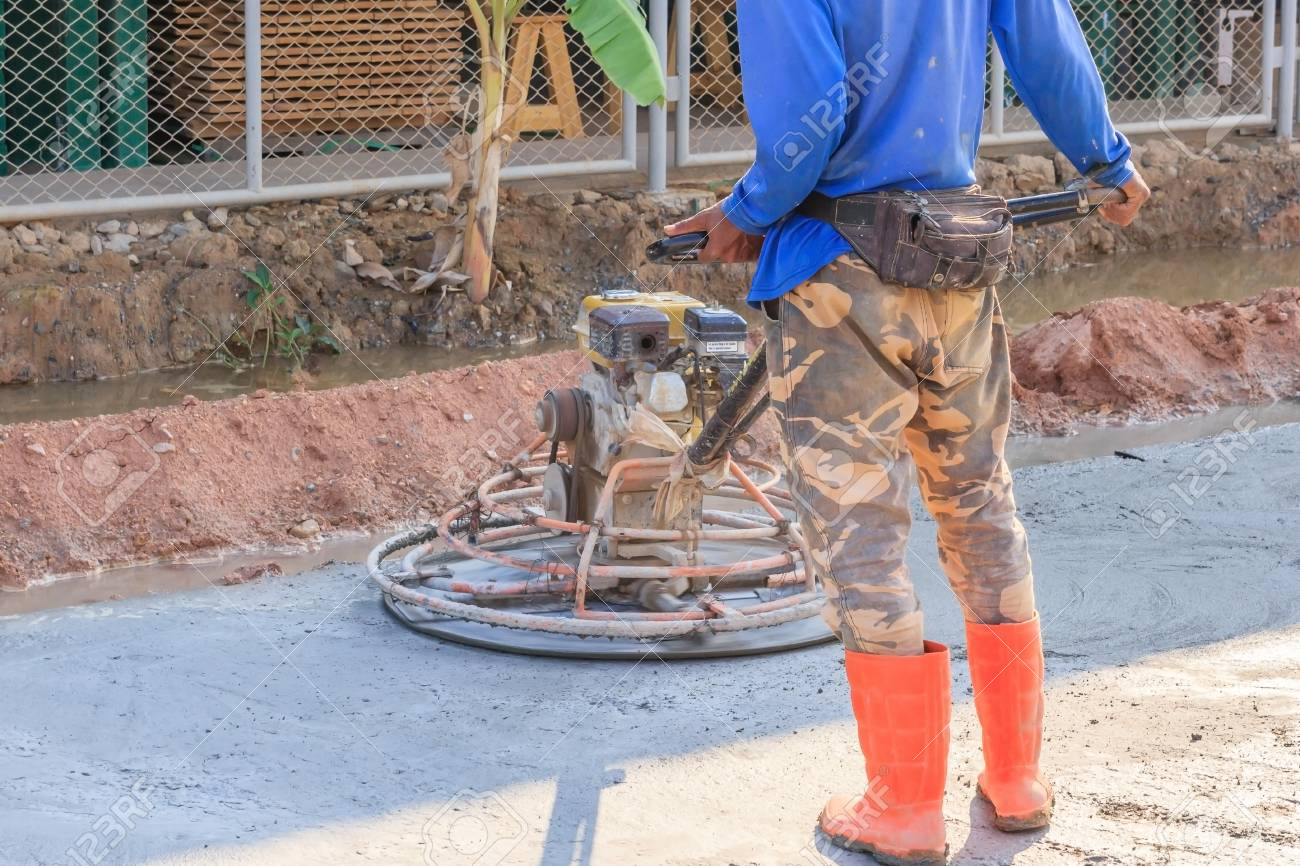Construction worker produces the grout and finish wet concrete