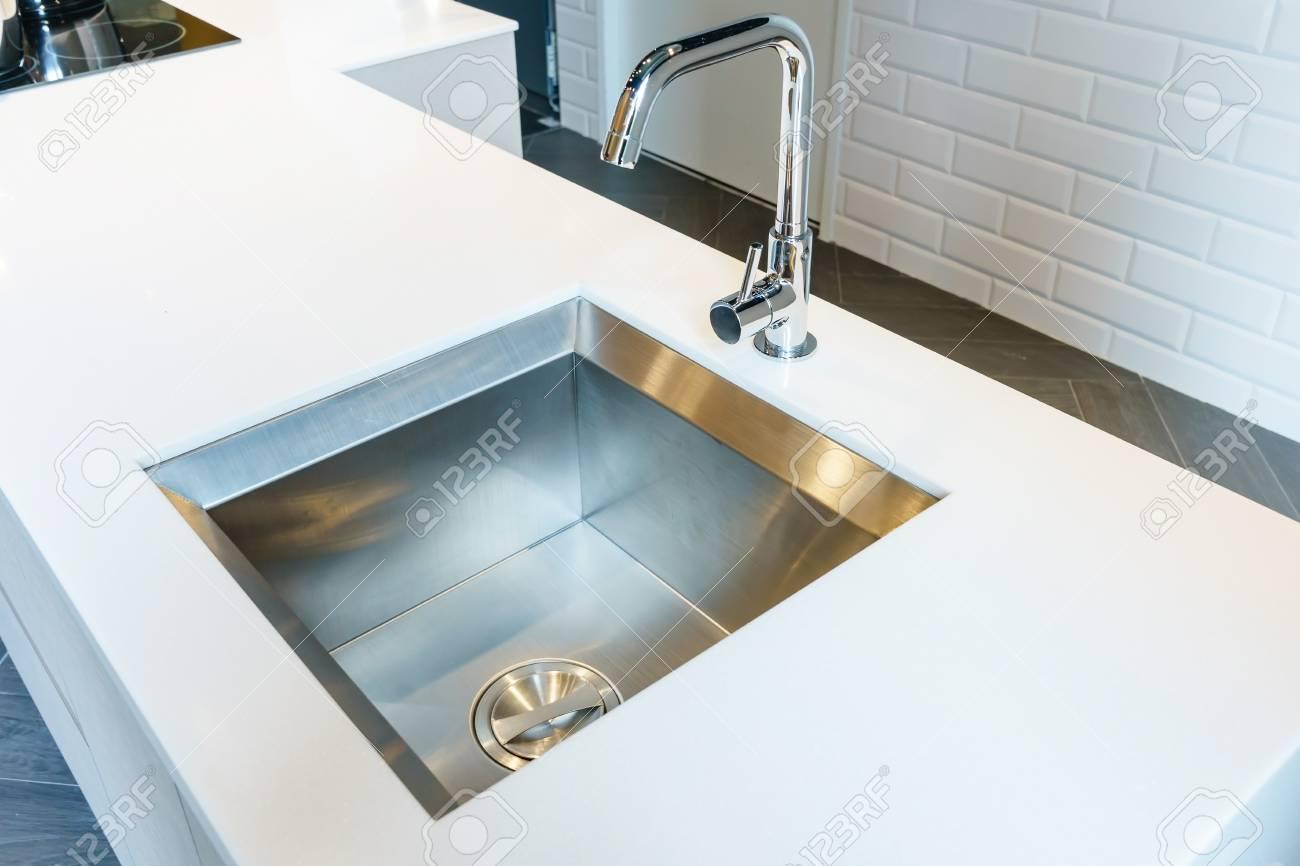 Detalle de un fregadero de cocina de diseño rectangular con grifo de agua  de cromo en encimera de granito de cocina blanca
