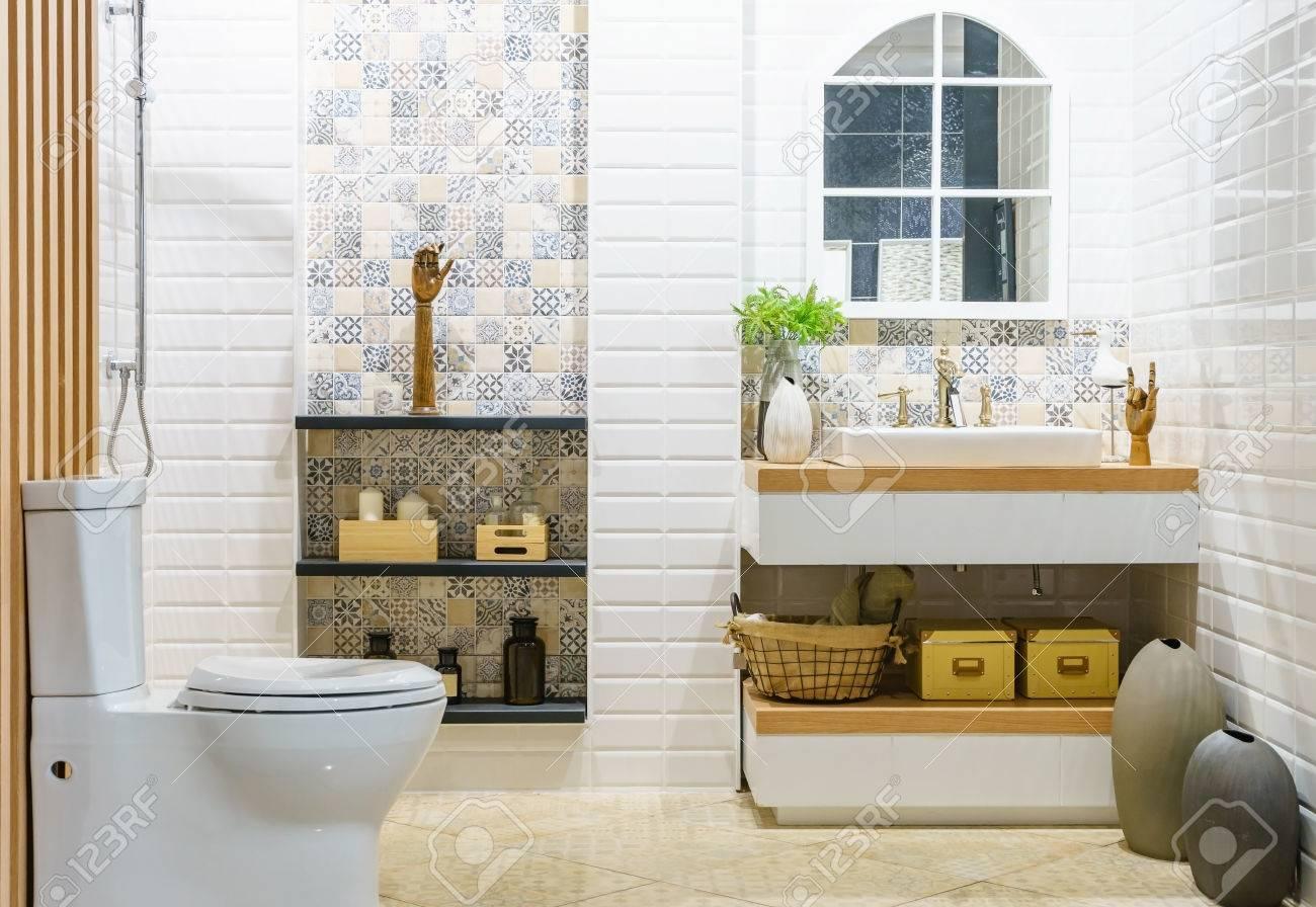 Salle de bain spacieuse moderne avec des carreaux lumineux avec WC et  lavabo. Vue de côté