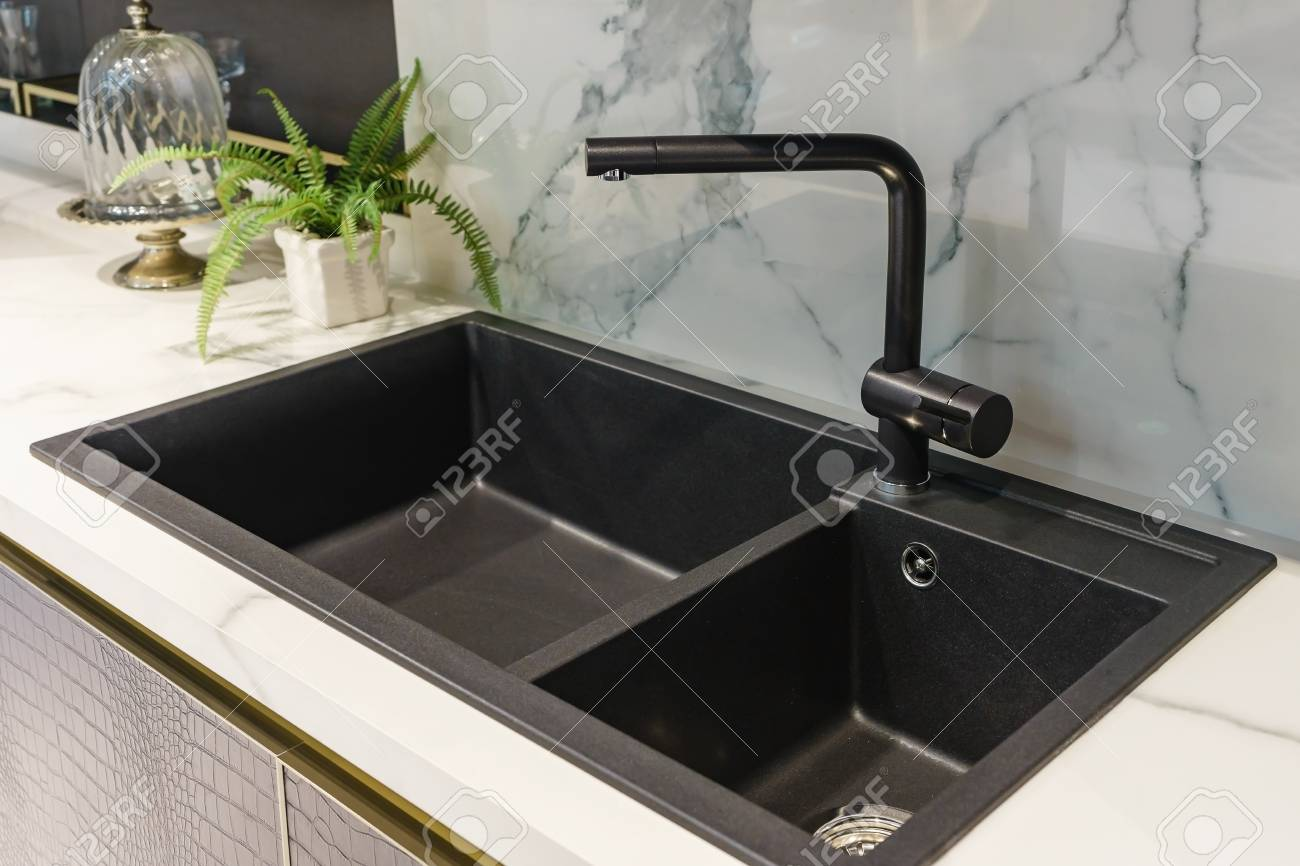 Black kitchen sink and Tap water in the kitchen. The interior..