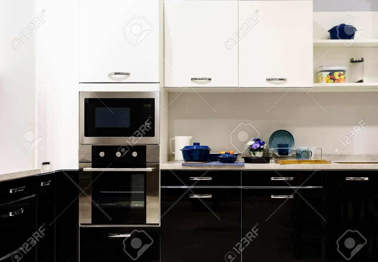 Muebles de cocina moderna con utensilios de cocina contemporánea como  estufa de inducción negro y horno de horno en la cena