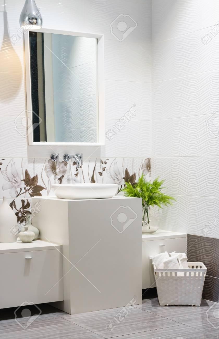 Specchio Per Lavandino Angolare chiuda su di un lavandino angolare in un interno di legno e bianco del  bagno. c'è una mensola nera con asciugamani bianchi e lampada