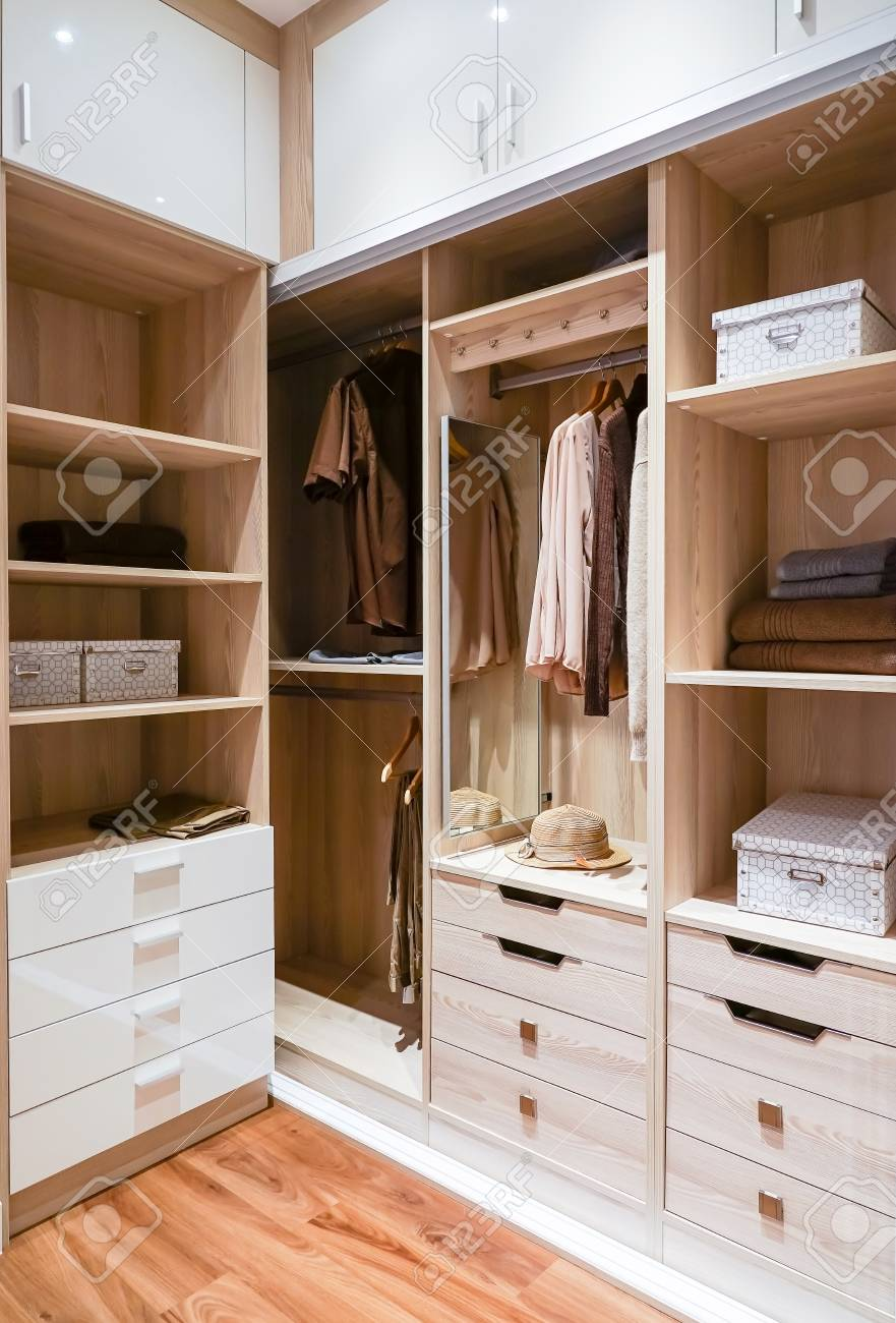Modern Wooden Wardrobe With Clothes Hanging On Rail In Walk In