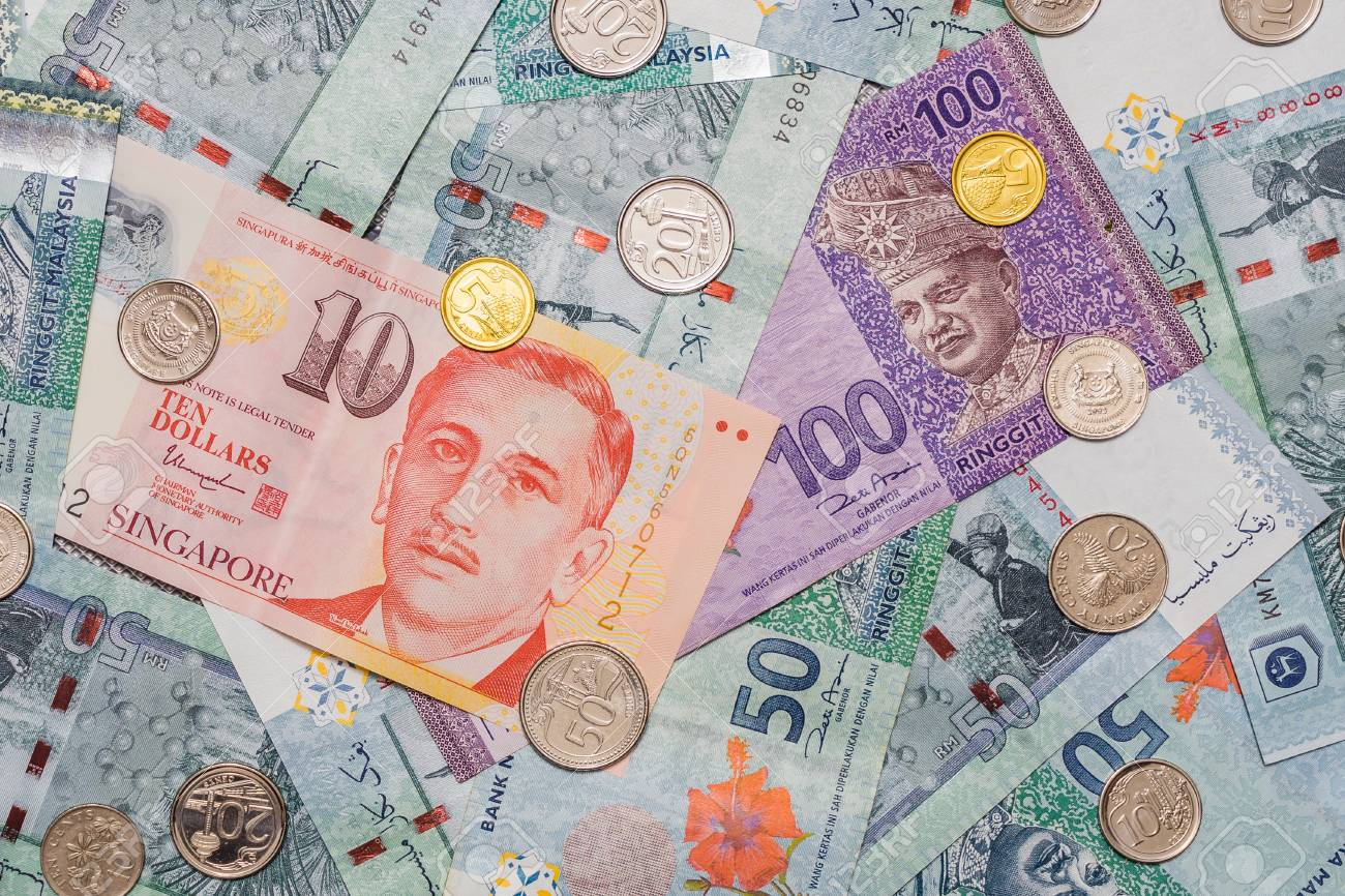 Singapore dollar and Coins on top of Malaysian Ringgit currency