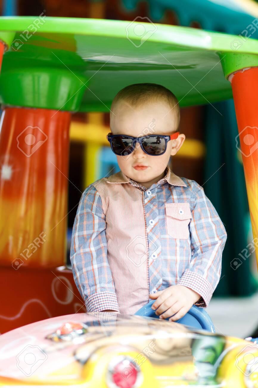 Little cute boy is having fun playing on a big toy car - 135258565