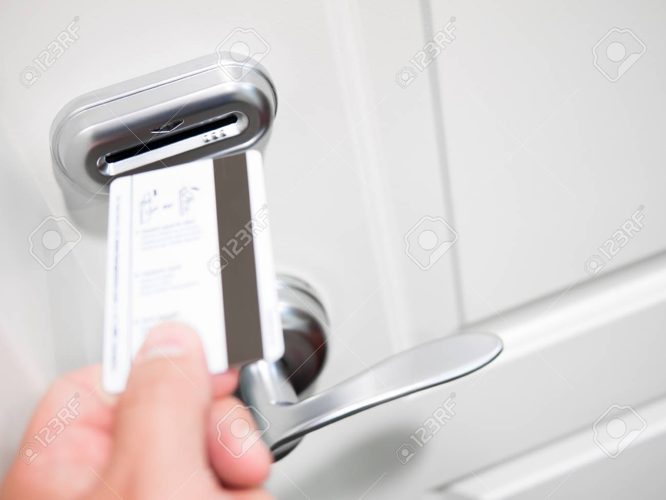 A person's hand inserting a keycard into an electronic door lock