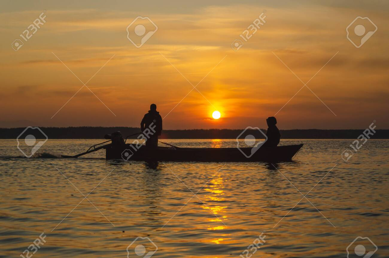 The fishermen and boat silhouette on the lake. - 148307445