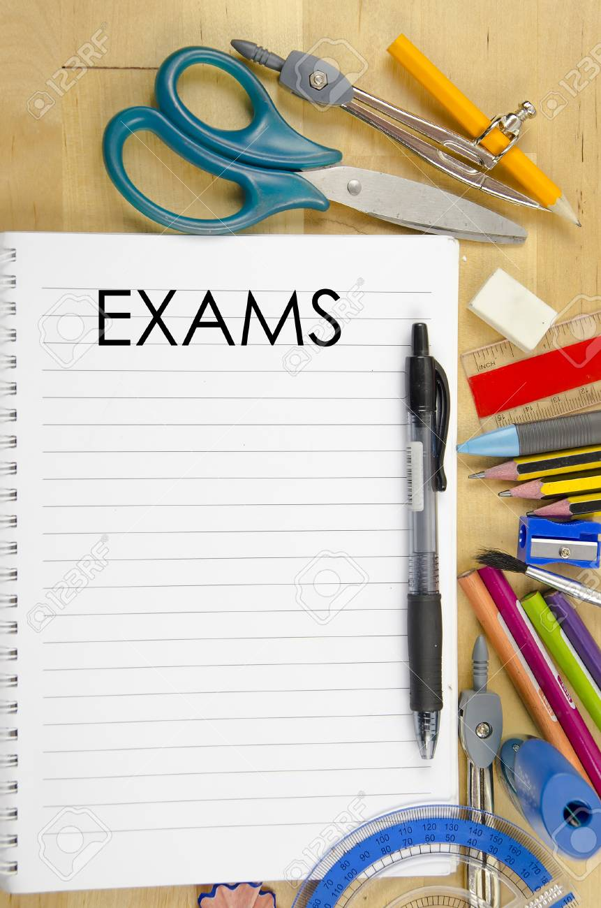 IMAGE OF NOTE BOOK WITH EXAMS WORDS ON WOODEN BACKGROUND WITH