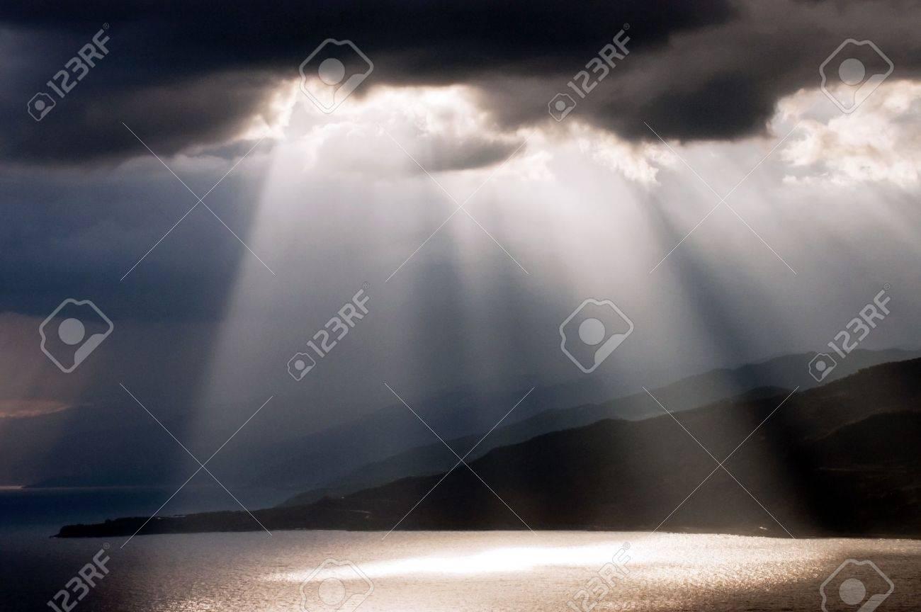 Sun shining through dark clouds on the sea Stock Photo - 15203218