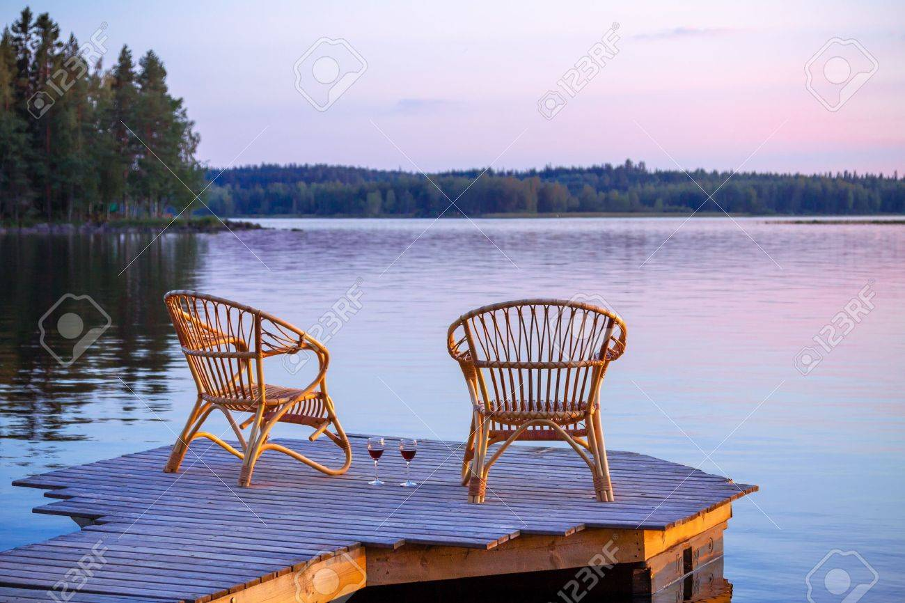 Gentil Stock Photo   Two Chairs On Dock With Glasses Of Wine