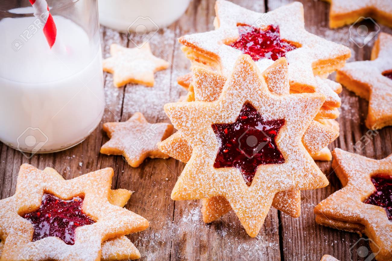 Christmas Linzer Cookies With Raspberry Jam On A Rustic Wooden