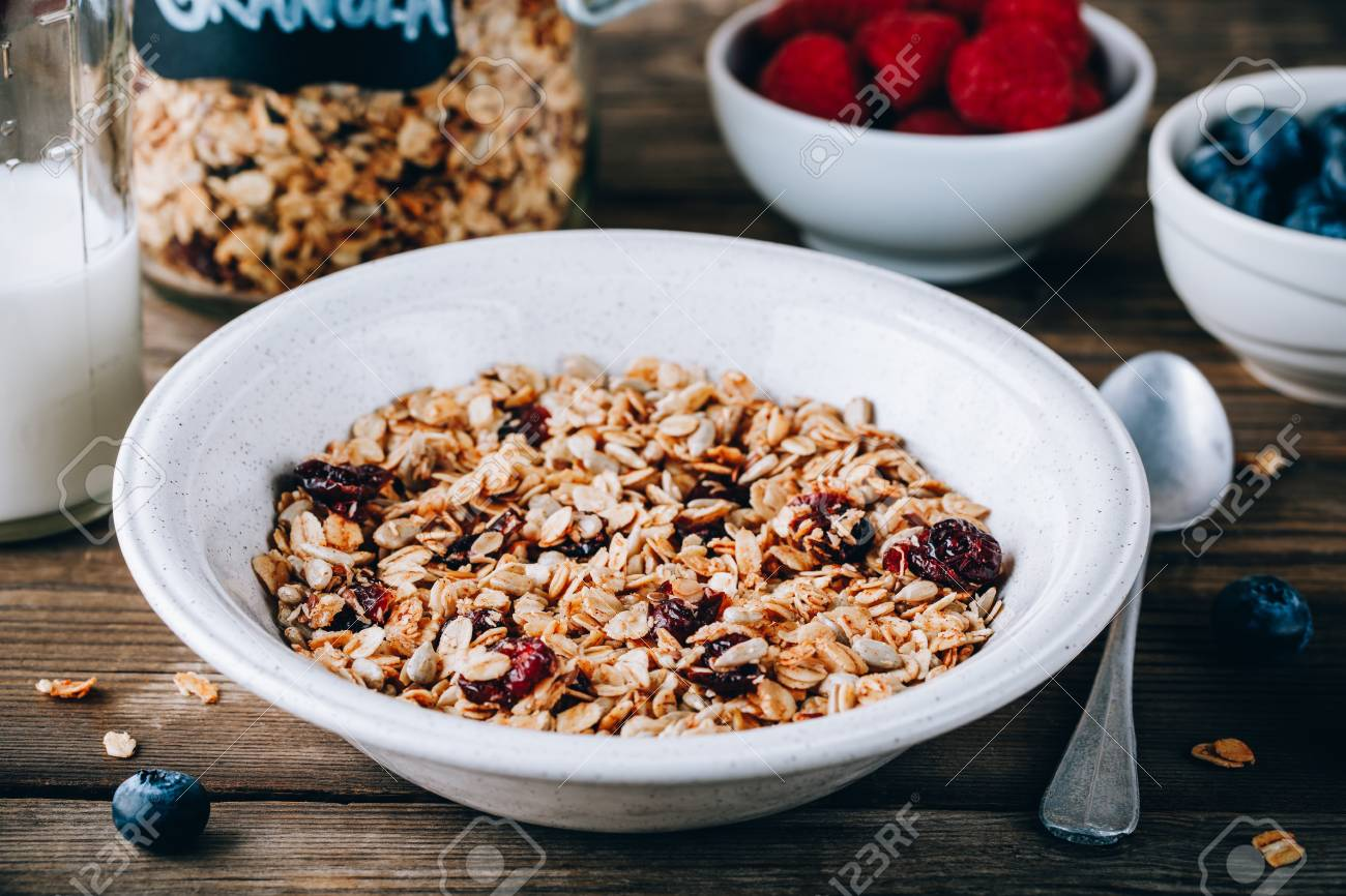 Organic homemade granola cereal with oats and nuts and dry cranberries. Healthy breakfast with milk