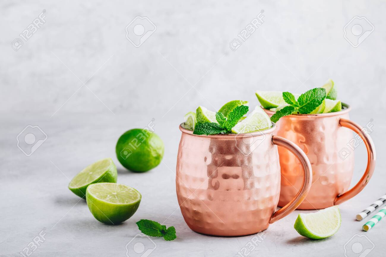 Moscow mule ice cold cocktail in copper cup with lime and and mint on gray stone background, copy space. - 126207124