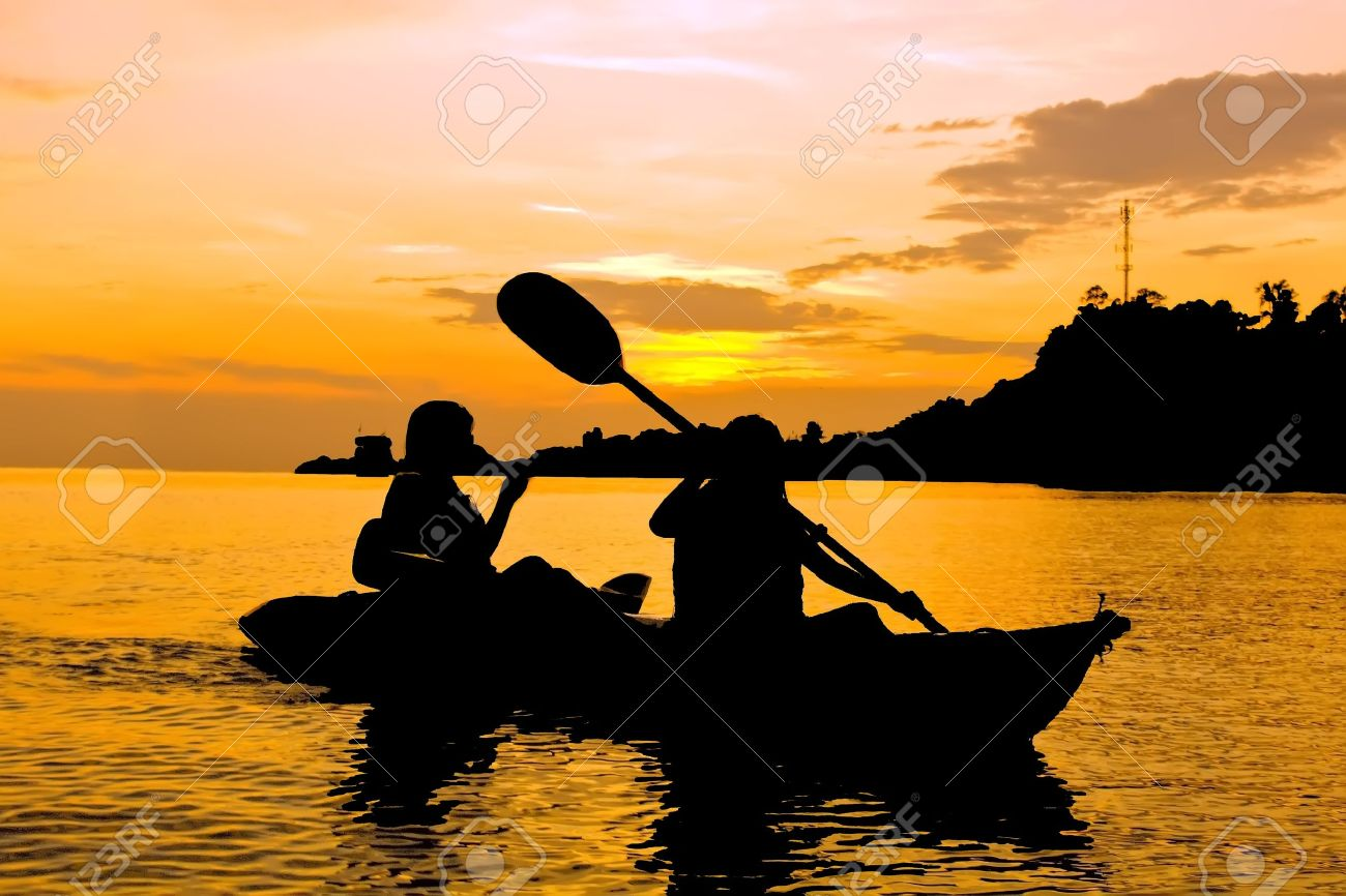 Silhouette Of Two Person Kayaking In The Sea At Sunset Koh Chang Thailand Stock Photo