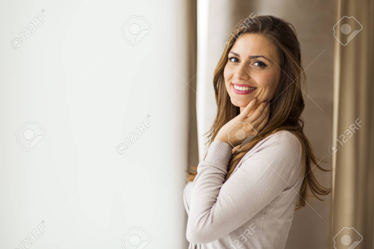 Beautiful And Successful Brunette Wife With Gorgeous Hair Posing In Front Of A Window Stock Photo