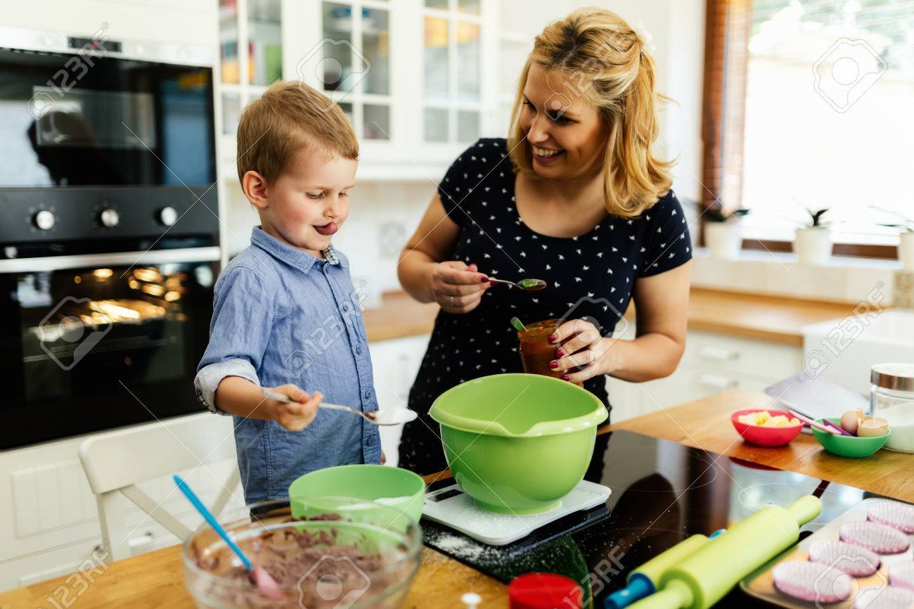 Child Helping Mother Make Cookies In Modern Kitchen Stock Photo   59584143