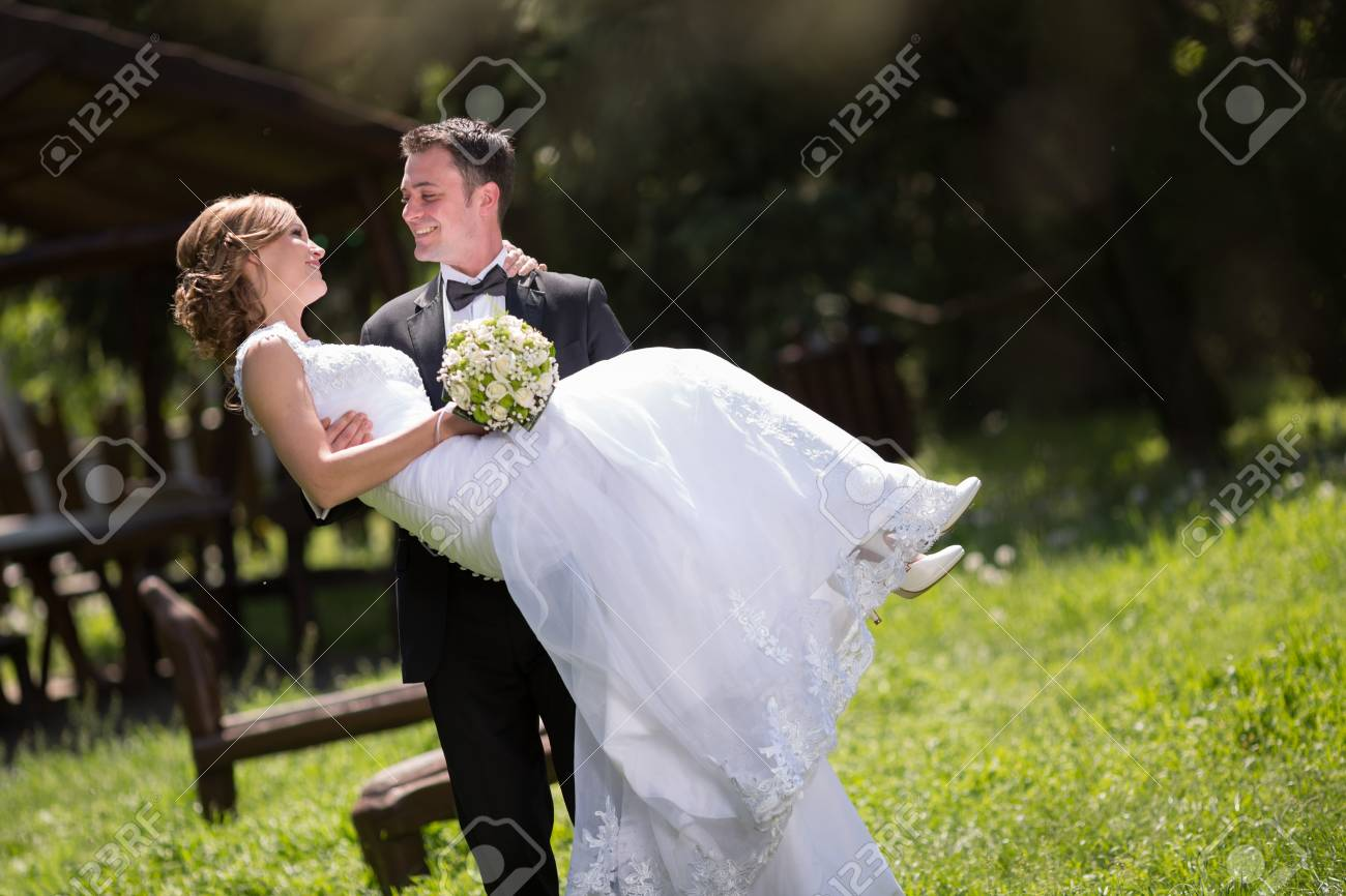 64452612-groom-carrying-bride-outdoors-a