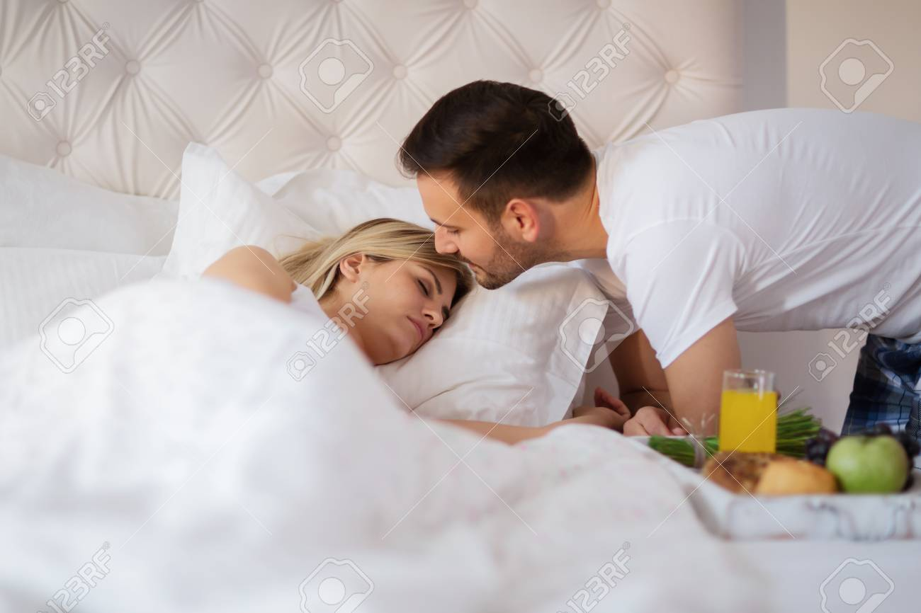 . Romantic husband waking wife with breakfast in bed