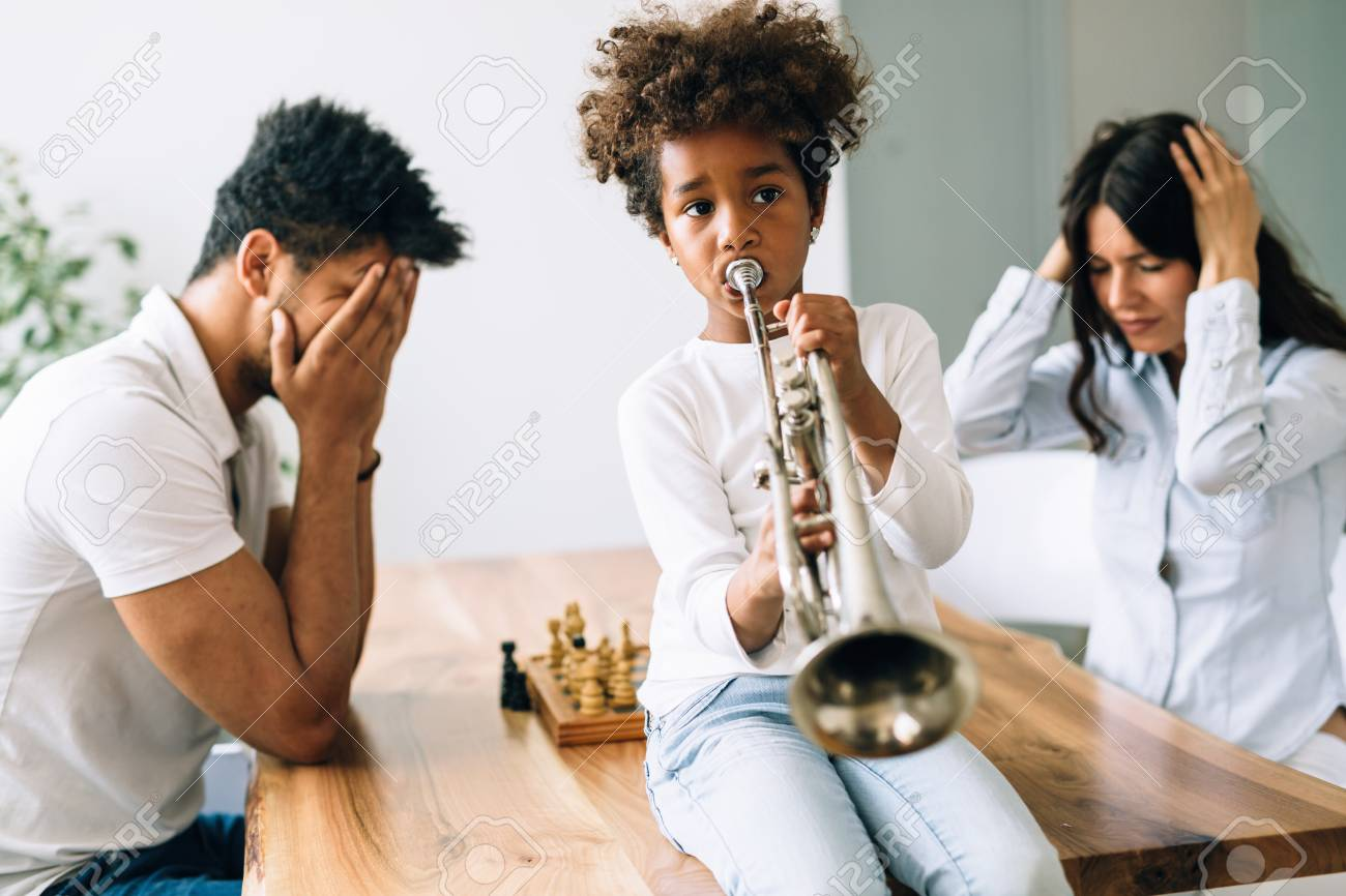 Picture of child making noise by playing trumpet in front of parents - 82268014