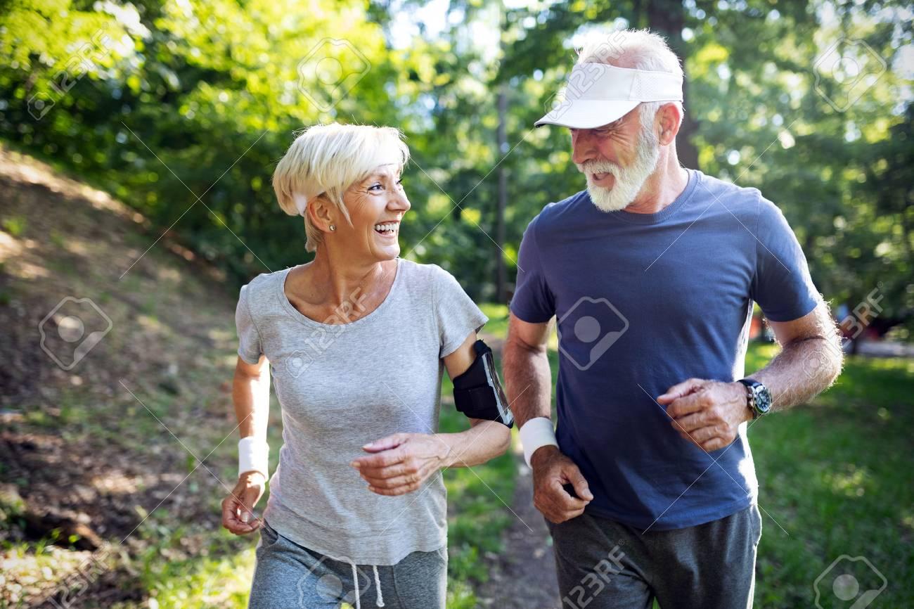 Happy fit senior couple exercising in park - 118420623