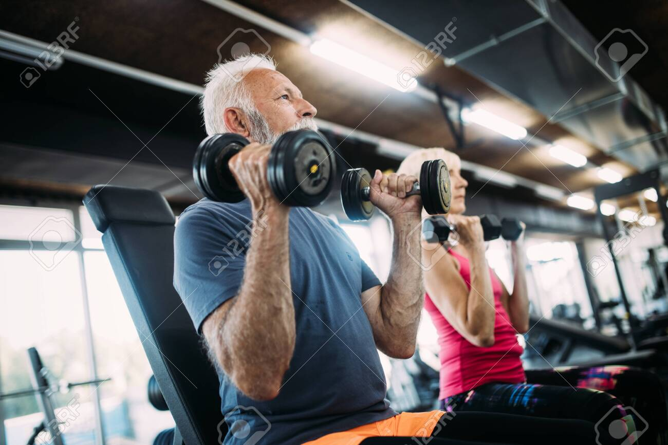 Mature fit couple exercising in gym to stay healthy - 120809981