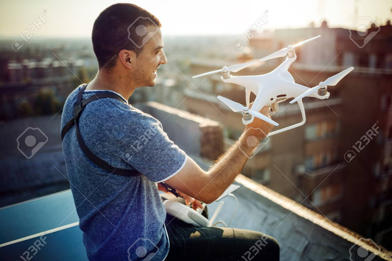 Young technician flying UAV drone with remote control on rooftop - 122451401