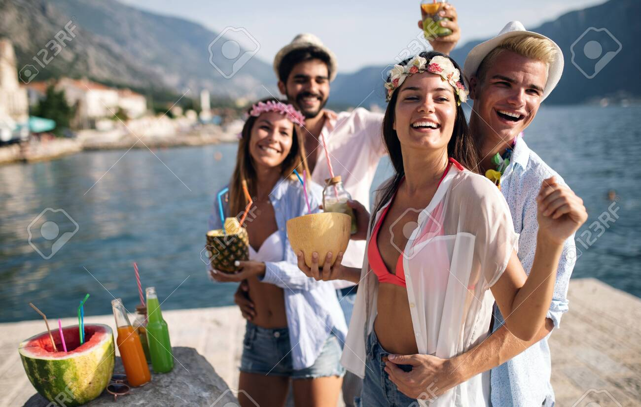 Group of friends having fun at summer party and drinking cocktail - 122930645