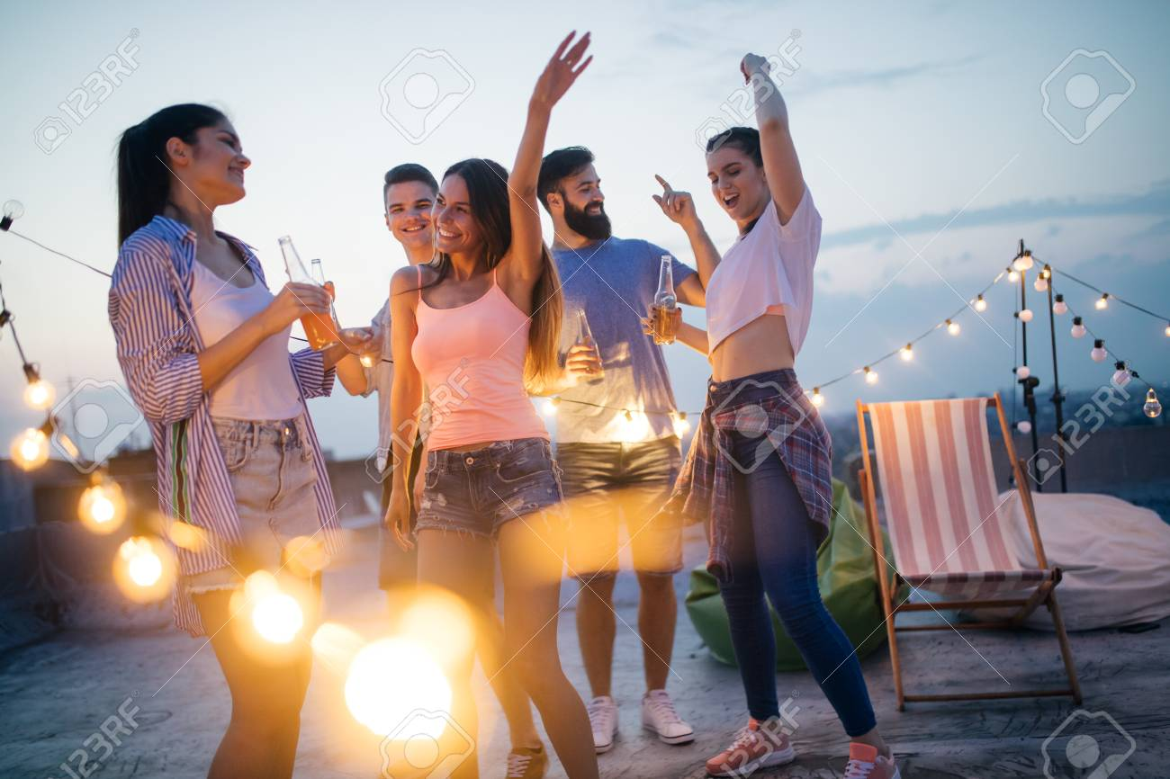 Happy friends with drinks toasting at rooftop party at night - 123856205