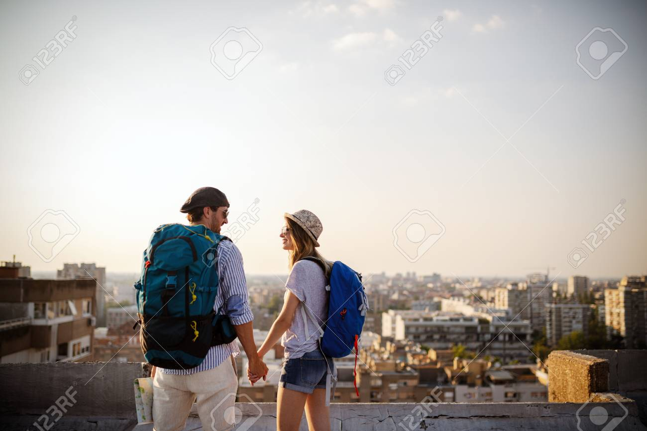Multiethnic traveler couple using map together on sunny day - 124789916