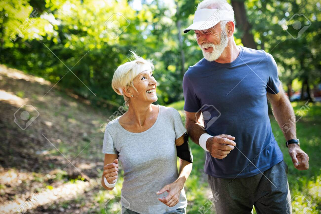 Mature couple jogging and running outdoors in nature - 124872182