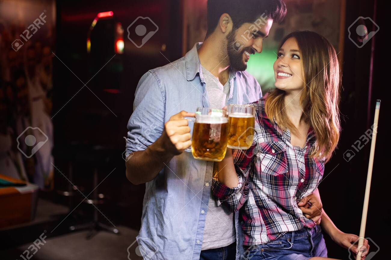 Couple drinking beer and playing snooker on date - 125263494