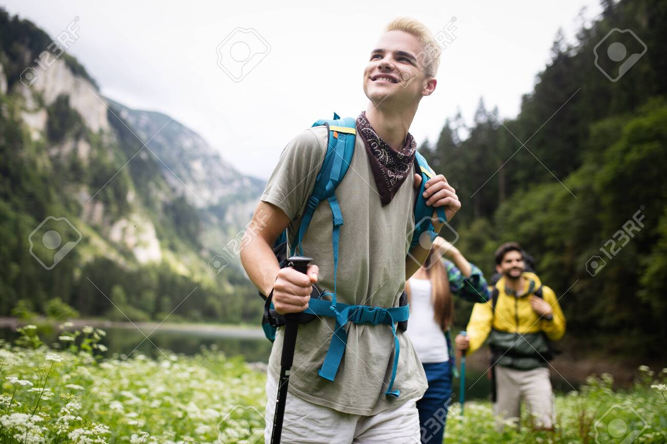 Group of happy friends with backpacks hiking together - 128009480