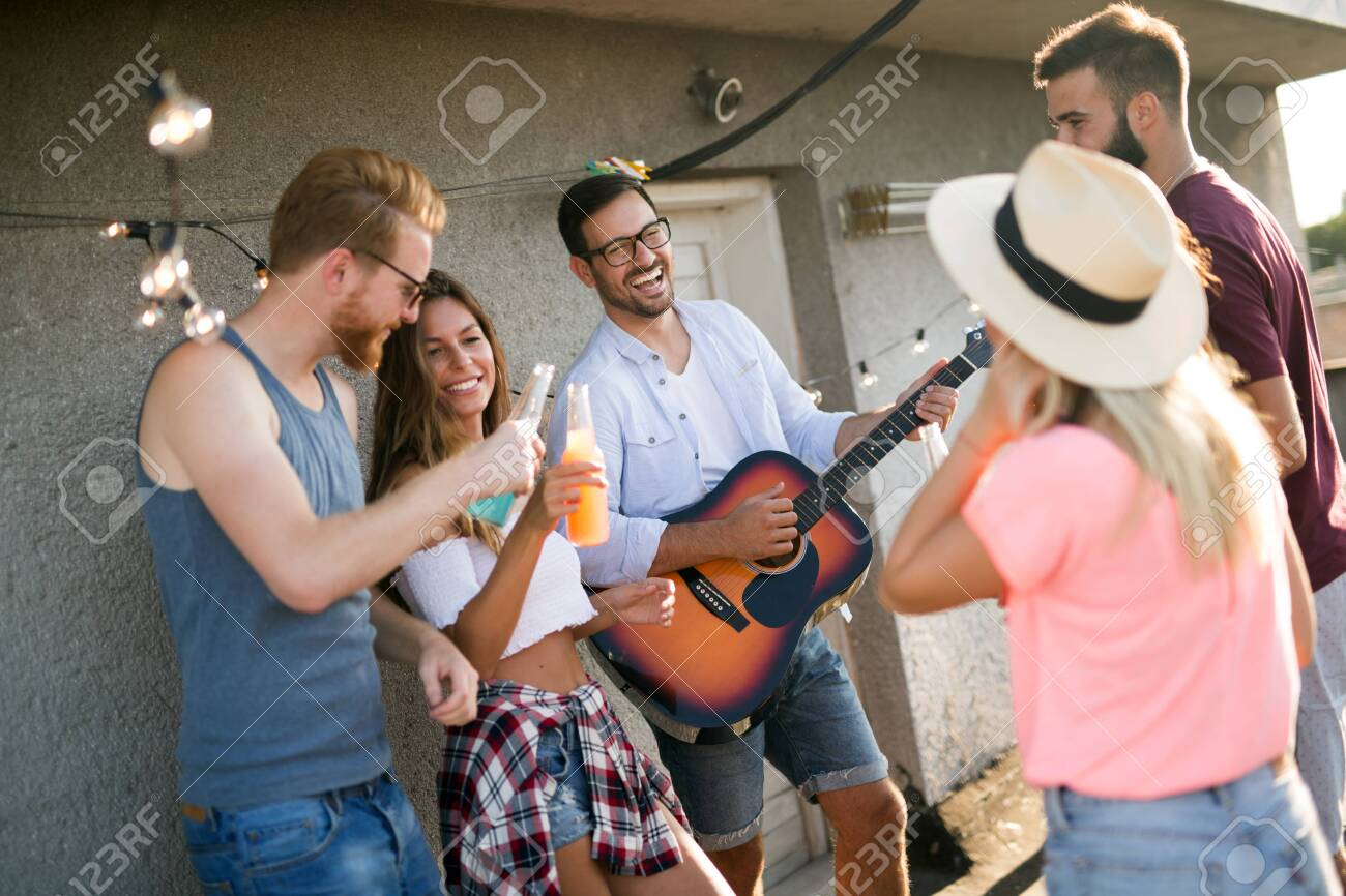 Group of happy friends having party on rooftop - 128970977