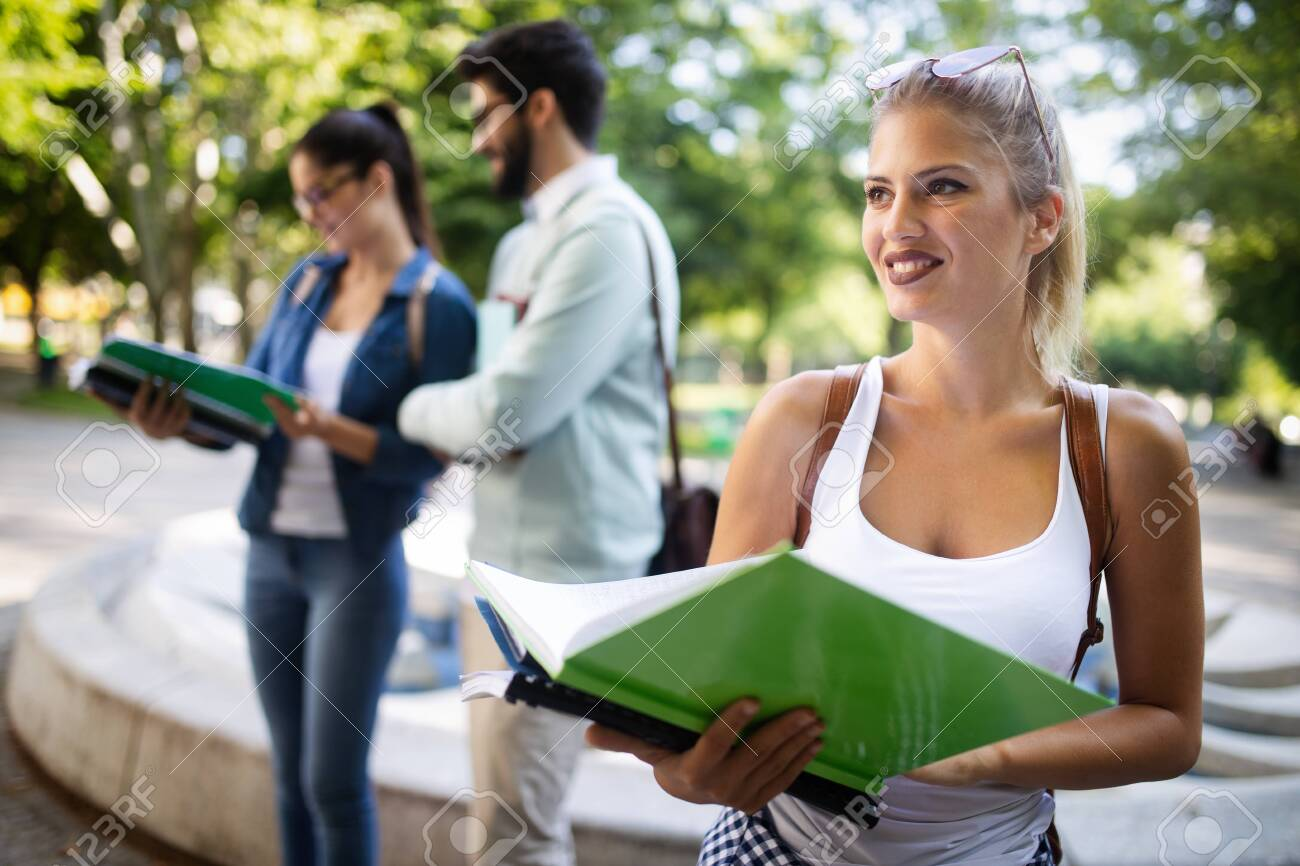Happy group of friends studying and talking together at university - 129471156