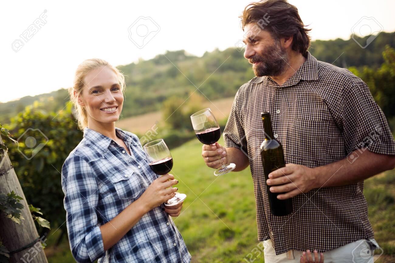 Wine growers tasting nice wine in vineyard - 129472162