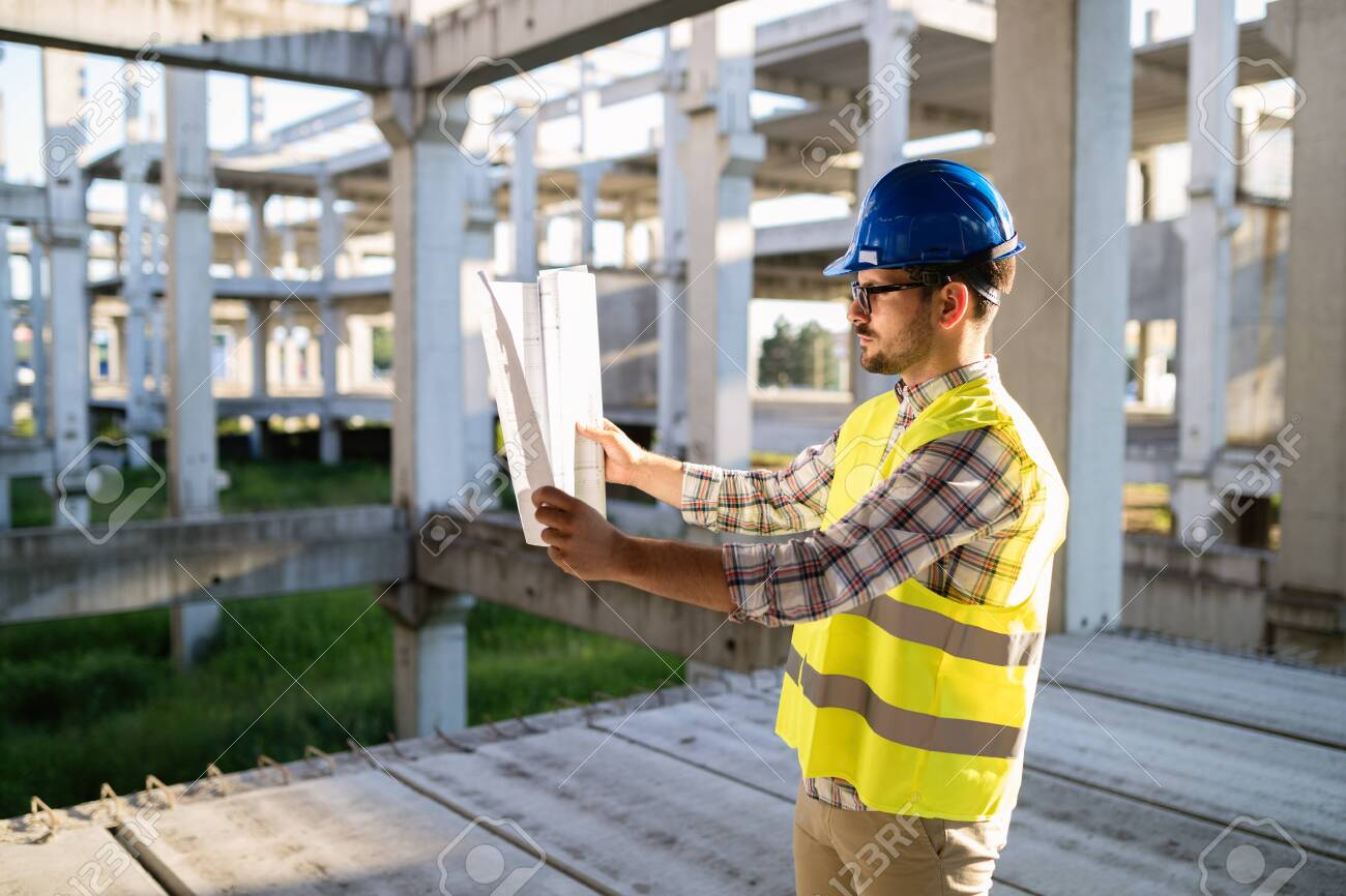 Engineer working on construction site and holding blueprint - 130935231