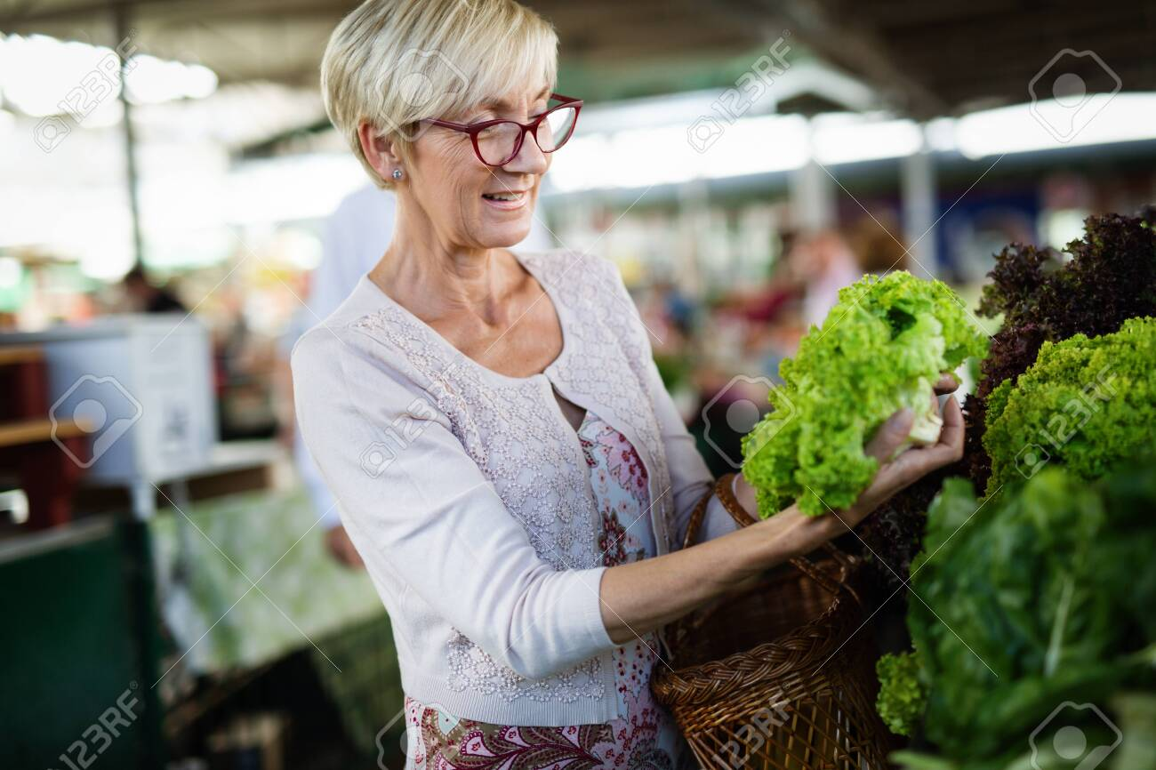 Picture of mature woman at marketplace buying vegetables - 133813786