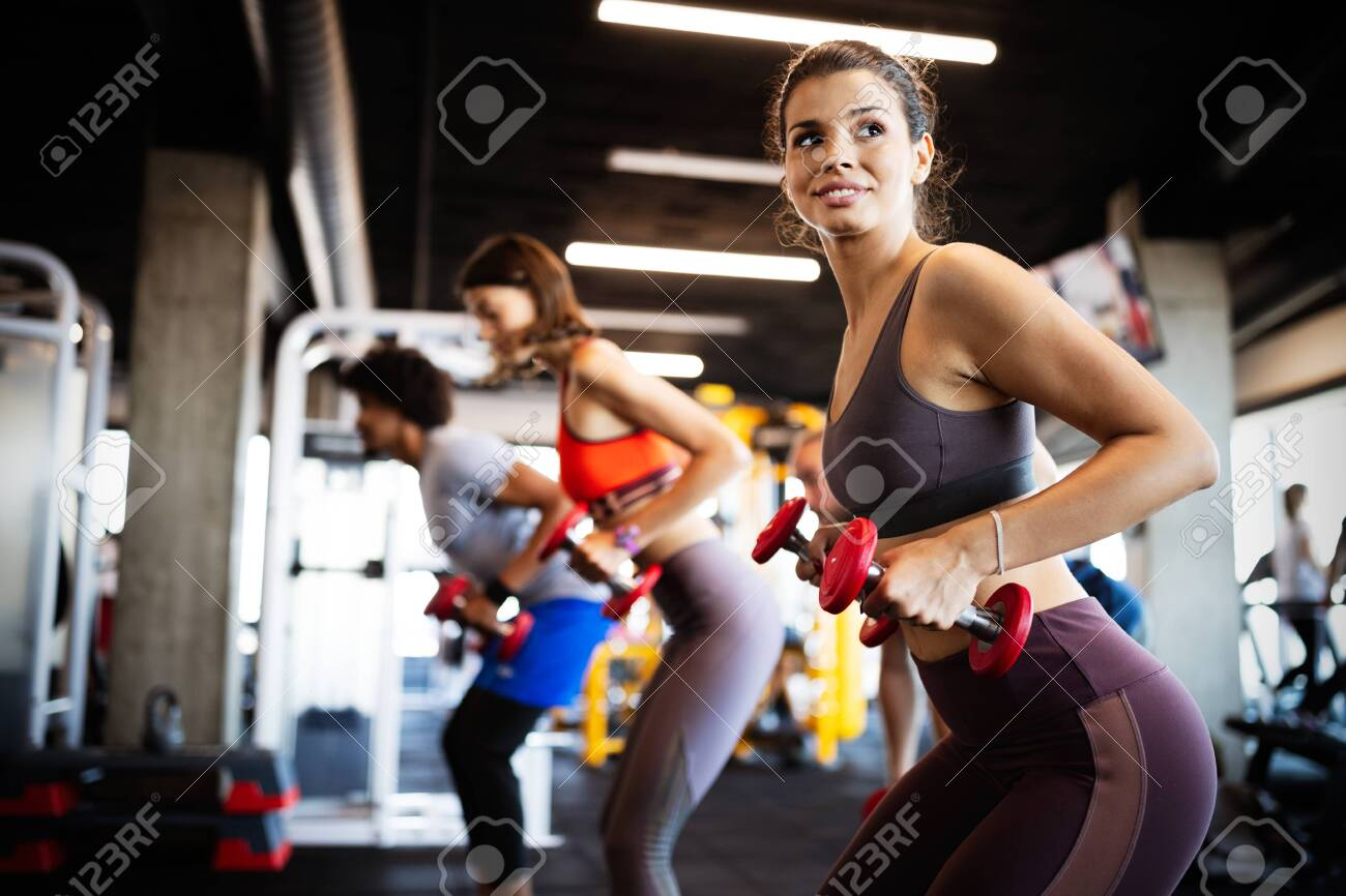 Healthy young people doing exercises at fitness studio. - 134280101