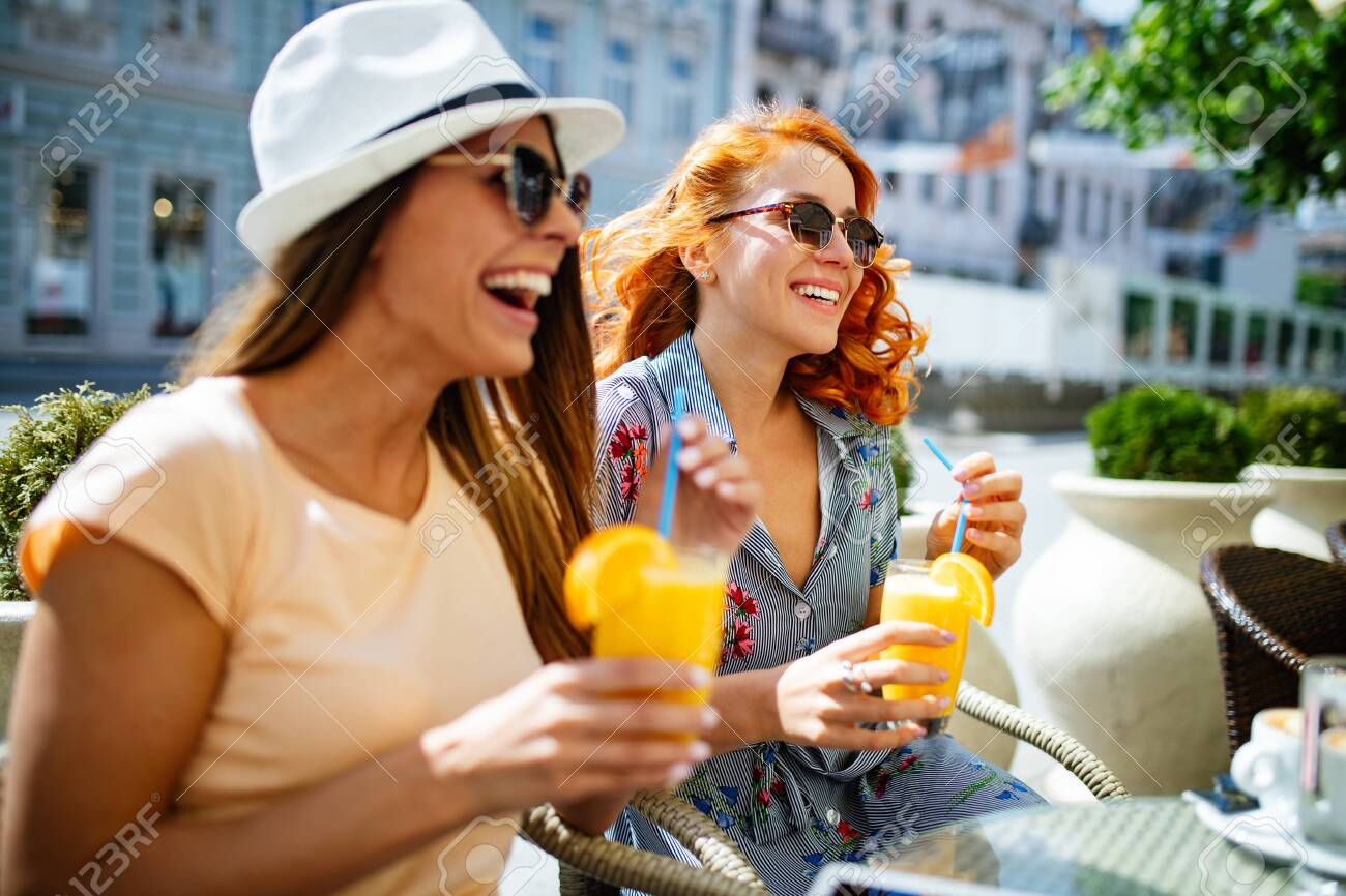 Friends having a great time in cafe. Women smiling and drinking juice and enjoying together - 138512750