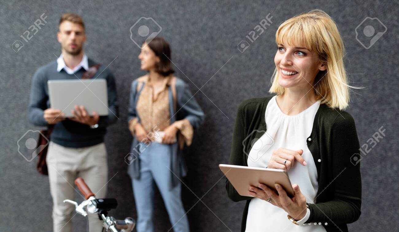 Group of young business people holding different digital devices outdoor - 148921041