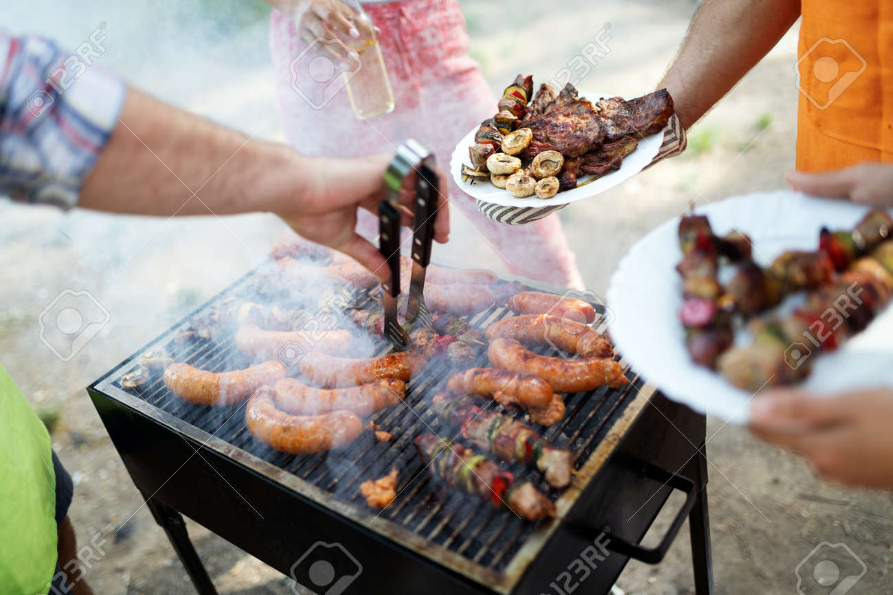 Selection of meat grilling over the coals on a portable barbecue - 152400964