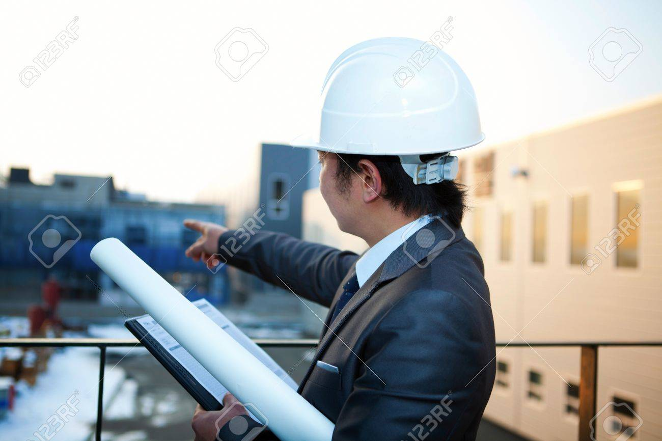 young architect with white helmet holding blueprint and clipboard pointing at the buiding construction Stock Photo - 17366359