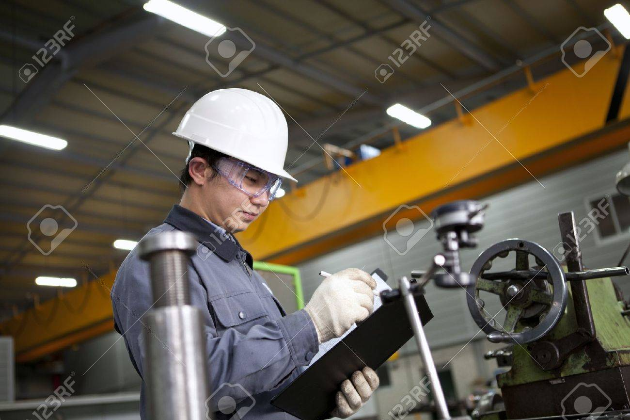 mechanical technician writing on notepad in the factory Stock Photo - 17366354